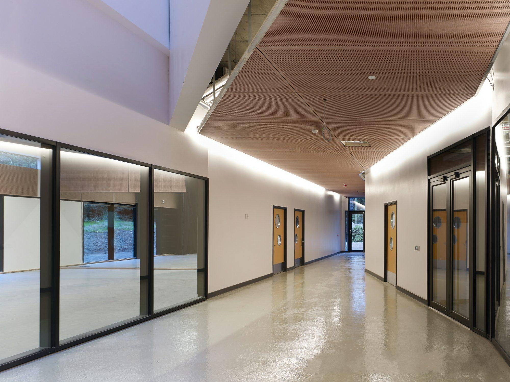 学院建筑是学校的教育风格的直接体现,如果具有自己独特的风格和创意,不仅可以形成学校的标志性建筑,也可以体现学院的教学规划意向,在英国诺维奇就建造了这么一个学院,落地面积2700平方米。    一层空间更多的使用了玻璃幕墙,增加了各处的可视性,穿过舞蹈教室便可以来到后花园,玻璃天窗的设计更是给舞蹈厅了的学生 了自然光线。二层的设计更像是一个大阁楼,开放的环境使人们仿佛置身与一个画廊中。透过穿孔的窗口可以看见外面的风景。在杆上的垂直尾翼遮挡较低层的西晒。   三层由特制地板打造的空间包括艺术表演排练厅、数字艺