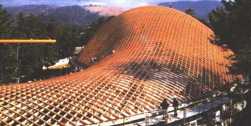 1988年建于奈良的丝绸之路博览会主展馆让我们看到了另一种新的木结构和空间形式。  奈良丝绸之路博览会主展馆   建筑采用了一种木造井字梁自由壳体的结构形式,这是由德国Frei otto教授及其合作者发明并首先在1975年的联邦庭园博览会多功能厅中使用且获得成功的一种结构形式。它使用小断面木材在地面加工成一定尺寸的正方形并字梁构架,然后吊起,各构架之间增加结构构件在空中进行连接固定,并利用木材所具有的柔韧性和变形能力,拼装成自山形态的空间构架。这是一种利用小断而木材进行大空间创造的结构方式,其特点为结构白