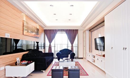 延续新古典设计元素,客厅电视柜以具木纹肌理且风格典雅的系统家具,搭配气派的银狐大理石电视墙,让整个空间显得落落大方。沙发背墙用木纹原色搭配中段的黑镜反射,并设计隐藏门,将佛堂入口隐身于其中。从背墙转到走道区,再以拉门做为卧房出入口。餐柜兼展示柜与客厅新古典设计相互呼应,延续黑镜的素材,让空间更有深度。在既有厨具配置外,刻意增设一个吧台,让厨房机能更齐全。黑白对比的设计,也从餐柜延伸至吧台区。由于喜欢紫色,因此餐厅特别挑选深紫色绒布餐椅,做为空间色彩点缀。入门处就运用手工雕凿的立体图腾,搭配雷射花纹玻璃